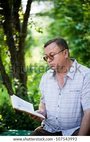 Relaxed casual man sitting in park and reading