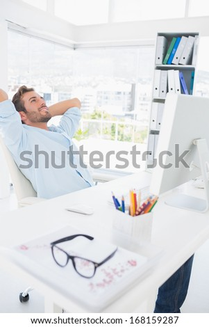 Relaxed casual young man resting with hands behind head in a bright office