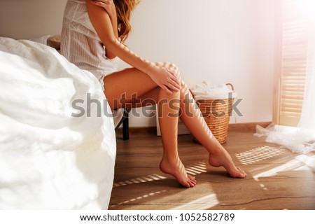 Relaxed Caucasian Girl is sitting on modern Bed with soft mattress near the window in light. She is enjoying a sunny Spring day and morning. Beautiful female Feet barefoot on the warm floor.