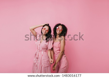 Relaxed caucasian girl playing with dark hair while posing with cute african lady. Indoor shot of stylish female models isolated on pink background