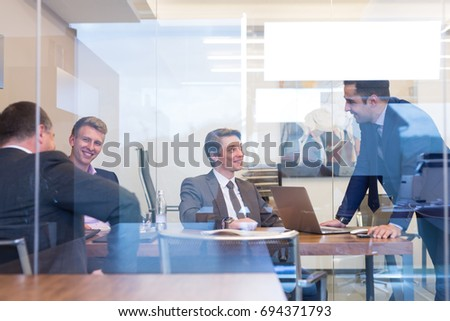 Relaxed cheerful business people sitting in friendly atmosphere and talking at informal corporate meeting. Team work and business success concept.
