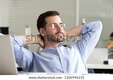 Relaxed confident business man taking break from work on laptop for mind relief holding hands behind head thinking of success enjoying rest, good result of job done in office, no stress free concept