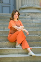 Relaxed confident trendy middle-aged woman in colorful orange ensemble sitting waiting on exterior steps looking down at the camera with a smile