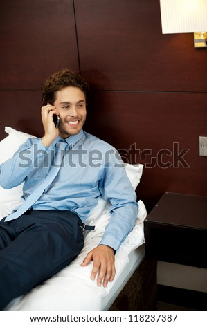 Relaxed cool guy talking on the phone after his long work day