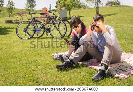 Relaxed couple in love using a smartphones sitting on the grass park at sunny summer day