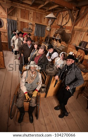 Relaxed customers in old west tavern with weapons at their sides