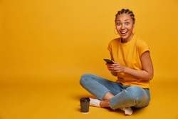 Relaxed dark skinned woman sits crossed legs, dressed in casual t shirt and jeans, uses mobile phone, sends text messages, browses internet, drinks takeaway coffee, scrolls news, isolated on yellow