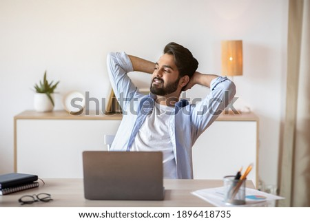 Relaxed Eastern Man Leaning Back In Chair, Resting After Online Work With Laptop, Millennial Arab Guy Sitting At Table With Computer In Home Office With Hands Behind Head And Looking Aside, Free Space