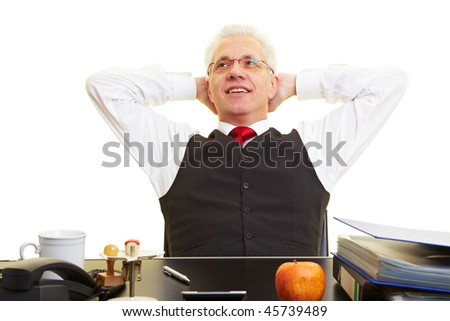 Relaxed elderly businessman leaning back at his desk