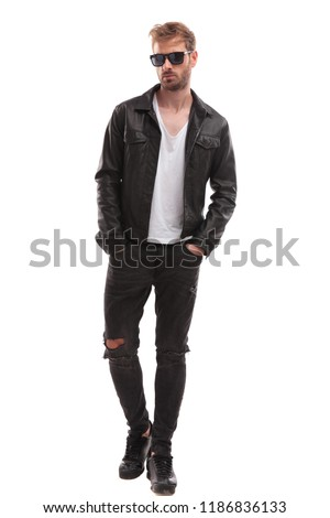 relaxed fashion man wearing sunglasses and black leather jacket walking on white background with hands in pockets and looking to side
