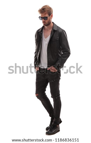 relaxed fashion man with sunglasses and black leather jacket walking on white background and looking down to side, full body picture