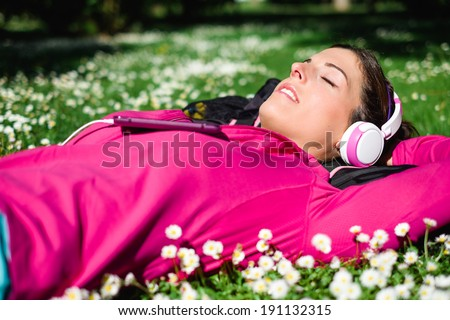 Relaxed female athlete resting and listening music with headphones after workout. Woman lying down on grass and spring flowers. Healthy lifestyle and happiness concept.