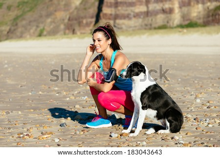 Relaxed fitness woman with dog listening music with sport arm band and earphones at the beach. Sporty girl taking a breath before running.