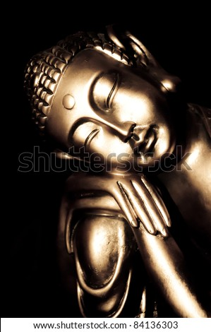 Relaxed golden buddha statue with a black background