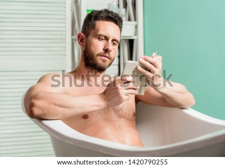 Relaxed guy reading book while relaxing in hot bath. Relax at home. Total relaxation. Personal hygiene. Nervous system benefit bathing. Relax concept. Man muscular torso relax bathtub and read book. #1420790255