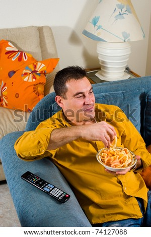 Relaxed guy watching television at home in the evening