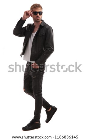 relaxed handsome man in black leather jacket steps to side on white background and fixes sunglasses, full length picture