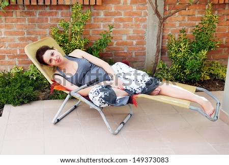 relaxed happy smiling pregnant young caucasian woman lying in outdoor chair outdoor