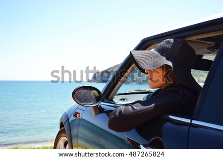 Relaxed happy woman on summer roadtrip travel vacation leaning out car window on blue sky background. #487265824