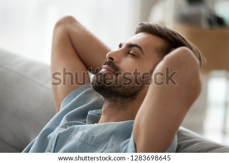 Relaxed happy young man resting having nap on comfortable couch breathing fresh air, lazy tired guy stretching enjoying stress free peaceful day feeling lounge mood at home, peace of mind concept