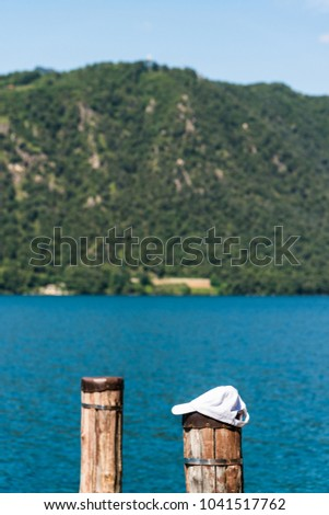 Relaxed lakeside scene with a white cap thrown over a wooden bollard with the opposite shore covered by trees in sight #1041517762