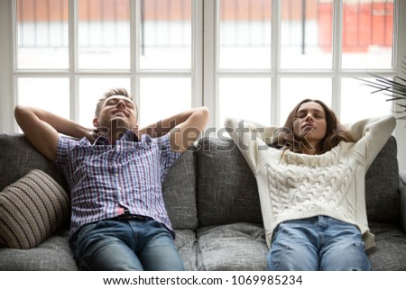 Relaxed man and woman enjoying relaxation or having nap at home on comfortable couch, happy young couple breathing fresh air meditating leaning on soft cushions of new sofa dozing on daytime together