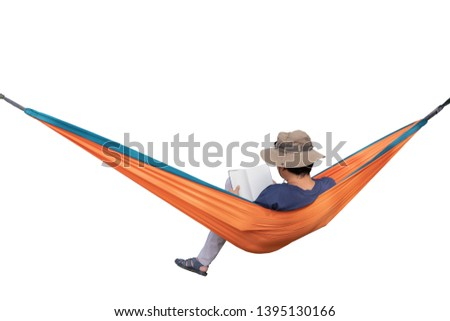 Relaxed man reading a book and lying in a comfortable hammock. Personal perspective of young man reading a book while relaxing on an hammock. People travel relaxation concept.