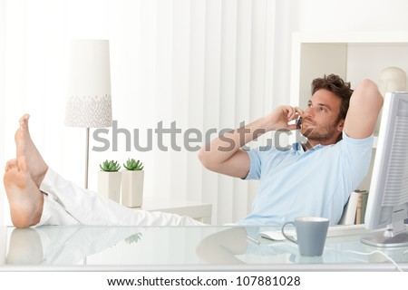 Relaxed man sitting with feet up on desk at home, talking on mobile phone, smiling.