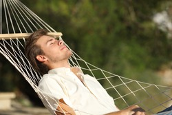 Relaxed man sunbathing resting lying on a hammock with eyes closed outdoors in the mountain