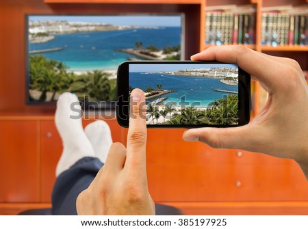 relaxed man with smartphone connected to a tv and envisioning photos in networking