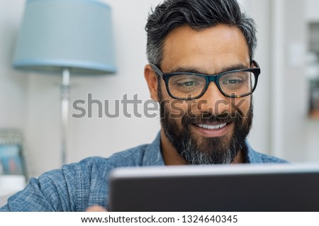 Relaxed mature man at home using digital tablet. Handsome hispanic man using laptop on sofa. Confident multiethnic guy with spectacles and beard using digital laptop.