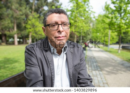 Relaxed middle-aged man sitting on bench in city park. Guy wearing casual clothes and relaxing with walkway and green trees in background. Relaxation and nature concept. Front view.