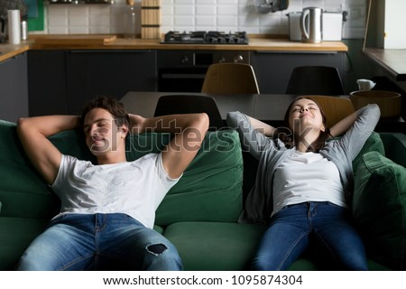 Relaxed millennial couple resting breathing fresh air on comfortable sofa together at home, happy young woman and man leaning on soft couch taking break for daytime peaceful nap dozing together