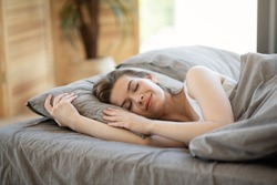Relaxed millennial girl sleeping on soft pillow in bed, indoors