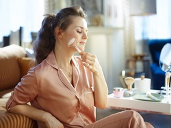 relaxed modern 40 years old woman in pajamas using calming quartz roller massager near table with toiletries in the modern living room in sunny winter day.