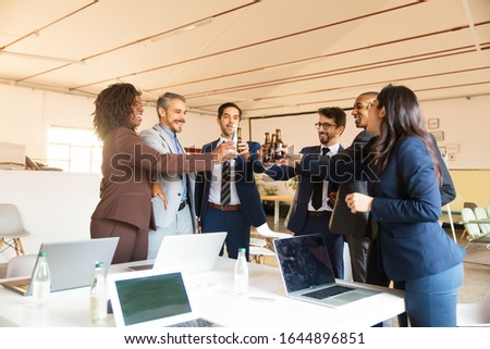 Relaxed office managers cheering with beer bottles. Cheerful young people relaxing after hard work. Relaxation concept