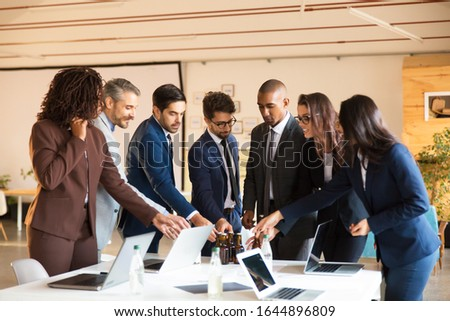 Relaxed office managers taking beer bottles from table. Cheerful young people relaxing after hard work. Relaxation, leisure concept