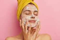 Relaxed pretty woman cares about her appearance, washes face with pleasant facial gel or soap, removes all pores, keeps eyes shut from pleasure, gets hygienic treatments, isolated on pink wall