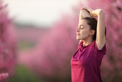 Relaxed runner stretching arms after exercise in a pink flowered field