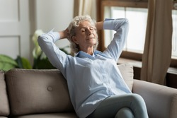 Relaxed 55s woman leaned on couch daydreaming in living room at home. No stress, enjoy fresh conditioned air, modern flat, maintain inner balance and harmony, healthy carefree comfortable life concept
