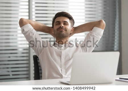 Relaxed satisfied positive calm lazy business man relax take break at work hold hand behind head sit at office desk dream rest from computer stretch feel no stress relief peace of mind at workplace