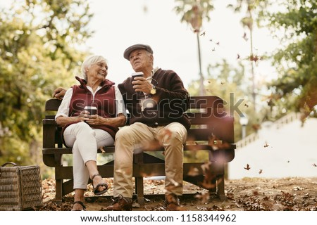 Relaxed senior couple on picnic sitting on park bench talking and having coffee. Old man and woman relaxing at park having coffee.