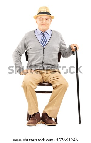 Relaxed senior man sitting on a wooden chair and looking at camera isolated on white background