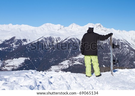 Relaxed snowboarder is looking on high mountains