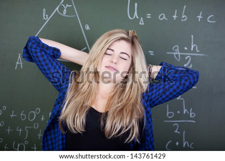 Relaxed student in class is stretching in front of blackboard