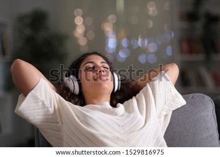 Relaxed tenant wearing headphones resting listening to music sitting on a couch in the living room in the night at home