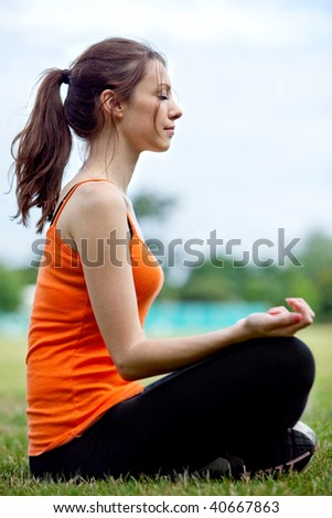 Relaxed thin woman practicing yoga at the park