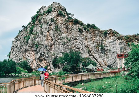 Photo of  Relaxed waterway amid limestone hills, featuring a suspension bridge, peddle boats  vendor carts.