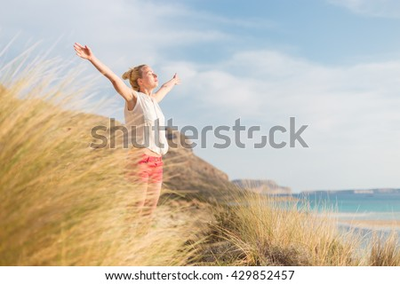 Relaxed woman, arms rised, enjoying sun, freedom and life an a beautiful beach. Young lady feeling free, relaxed and happy. Concept of vacations, freedom, happiness, enjoyment and well being. #429852457