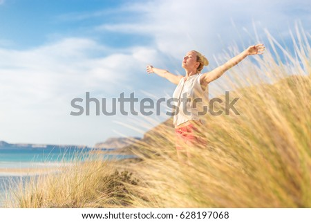 Relaxed woman, arms rised, enjoying sun, freedom and life an a beautiful beach. Young lady feeling free, relaxed and happy. Concept of vacations, freedom, happiness, enjoyment and well being. #628197068